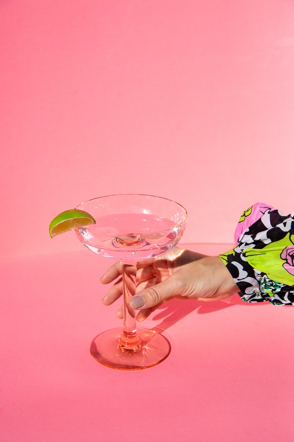 person holding clear wine glass with pink liquid