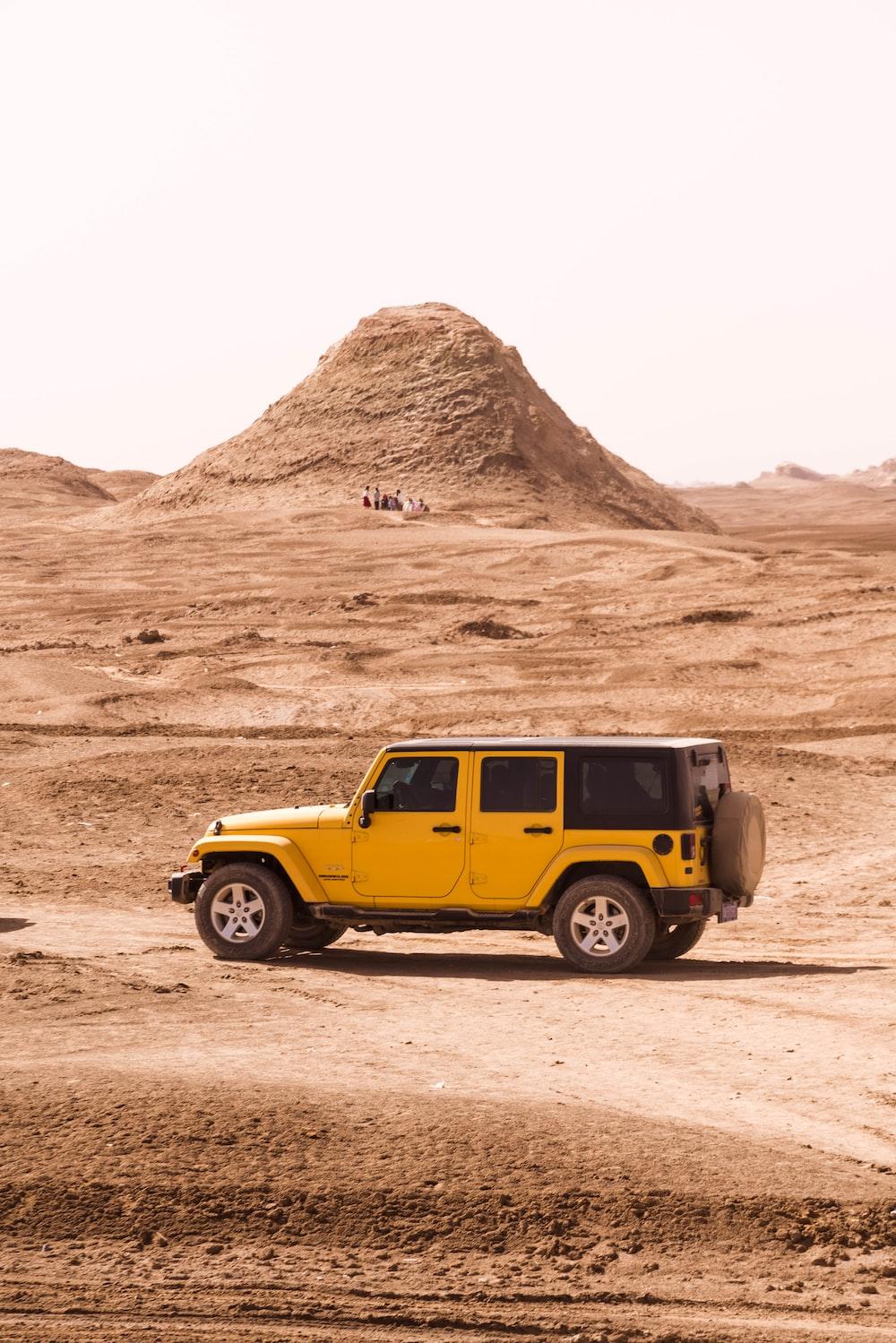 yellow suv on brown sand