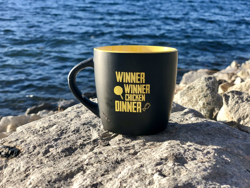 black and yellow ceramic mug on gray rock near body of water during daytime