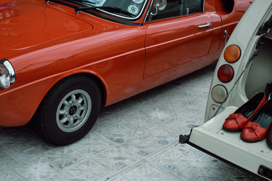 Red Car On White and Gray Floor Tiles - unsplash