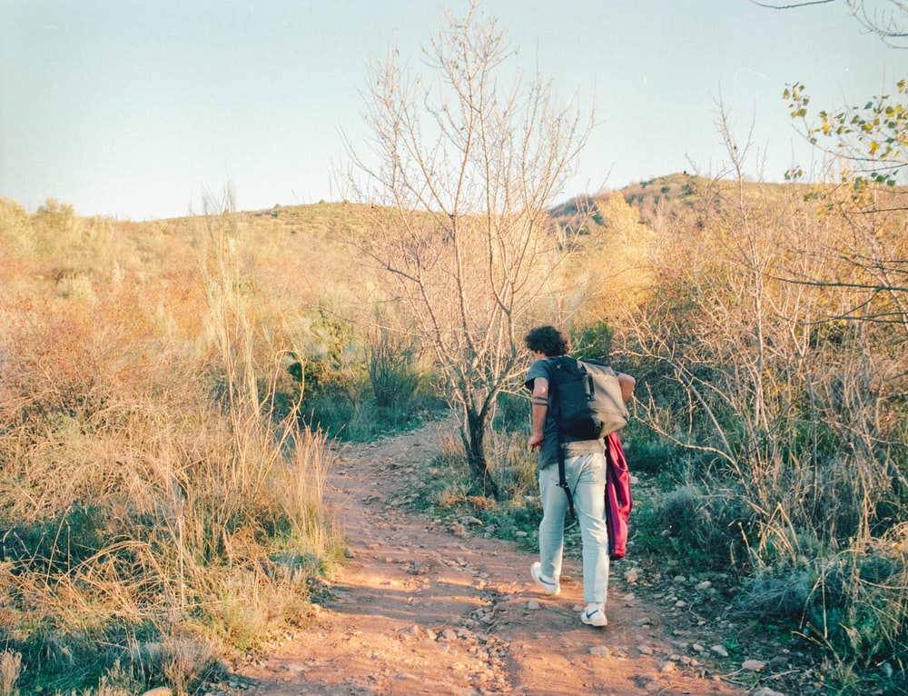 woman in black jacket and blue denim jeans walking on dirt road between brown grass field