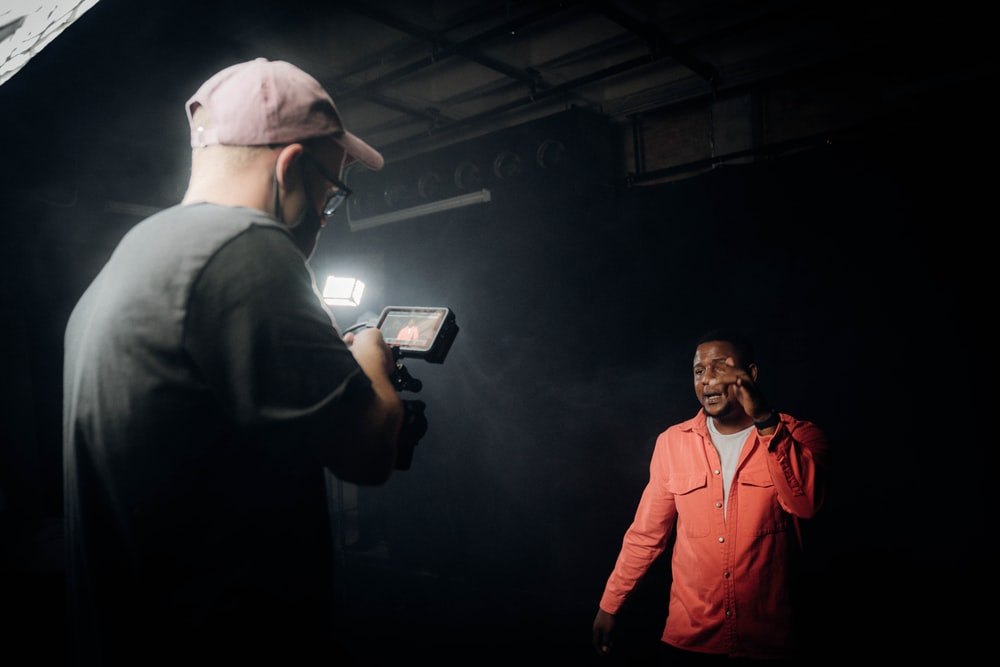 man in orange jacket standing beside man in black suit