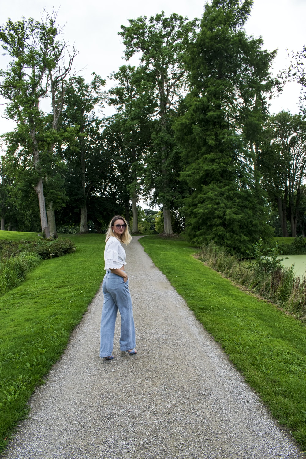 woman in white long sleeve shirt and blue denim jeans standing on gray asphalt road during