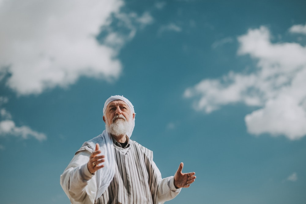 man in white and black striped dress shirt under blue sky during daytime