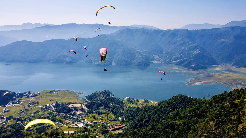 people on parachute over green mountains during daytime