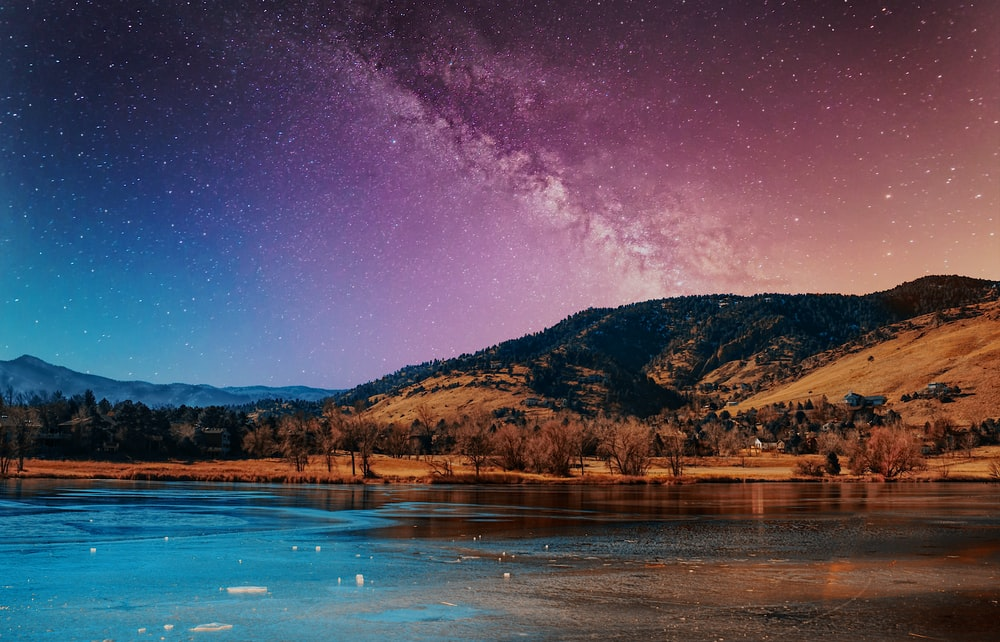 brown mountain beside body of water during night time