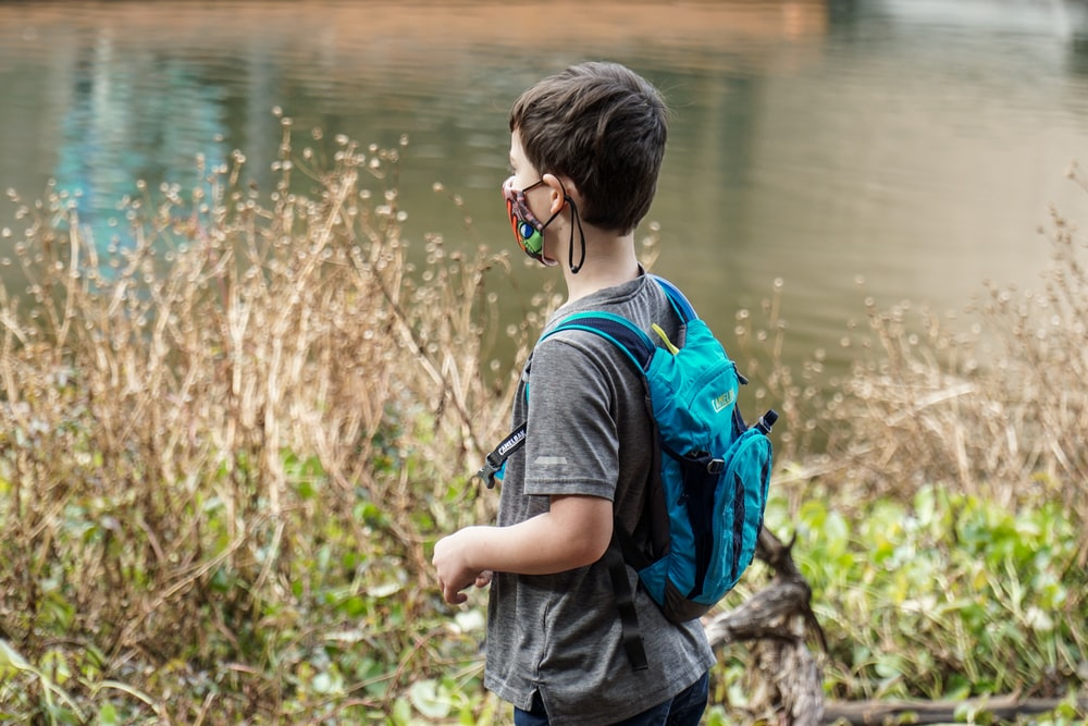 boy in blue and black backpack standing near body of water during daytime