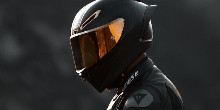 black and orange helmet on black motorcycle