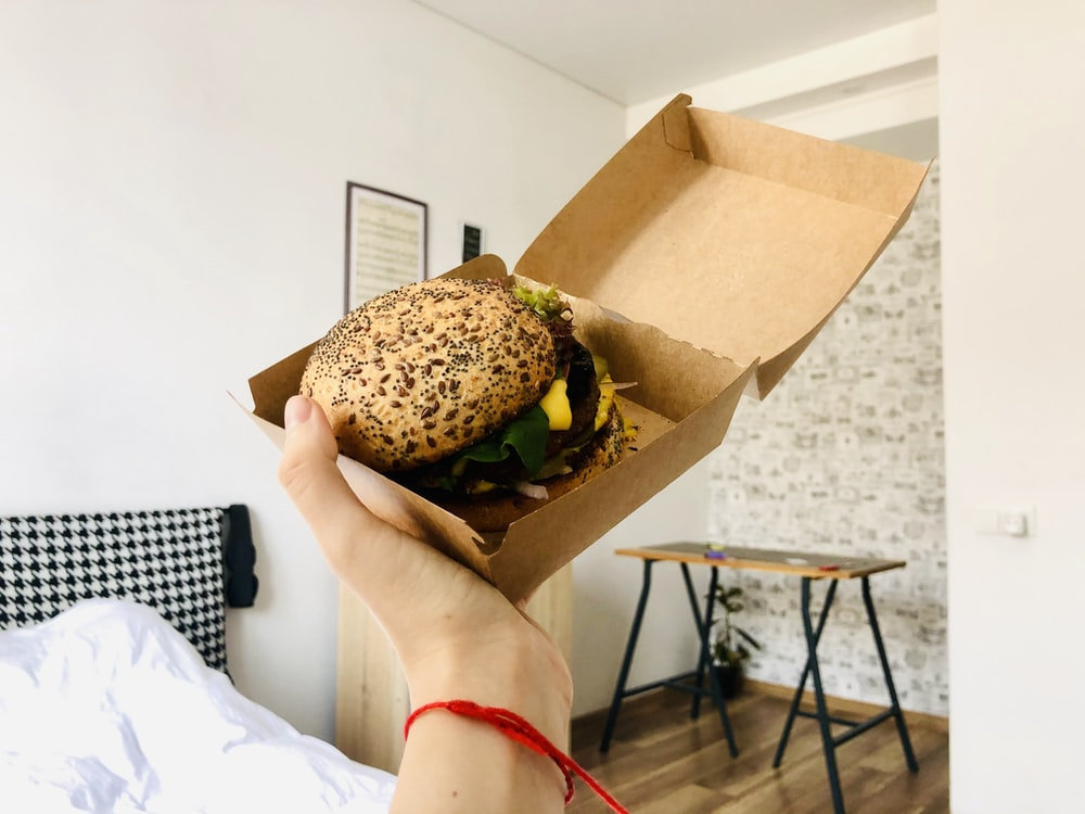 person holding burger with lettuce and cheese