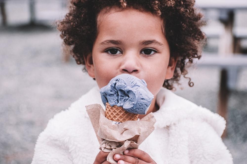 girl in white sweater holding ice cream