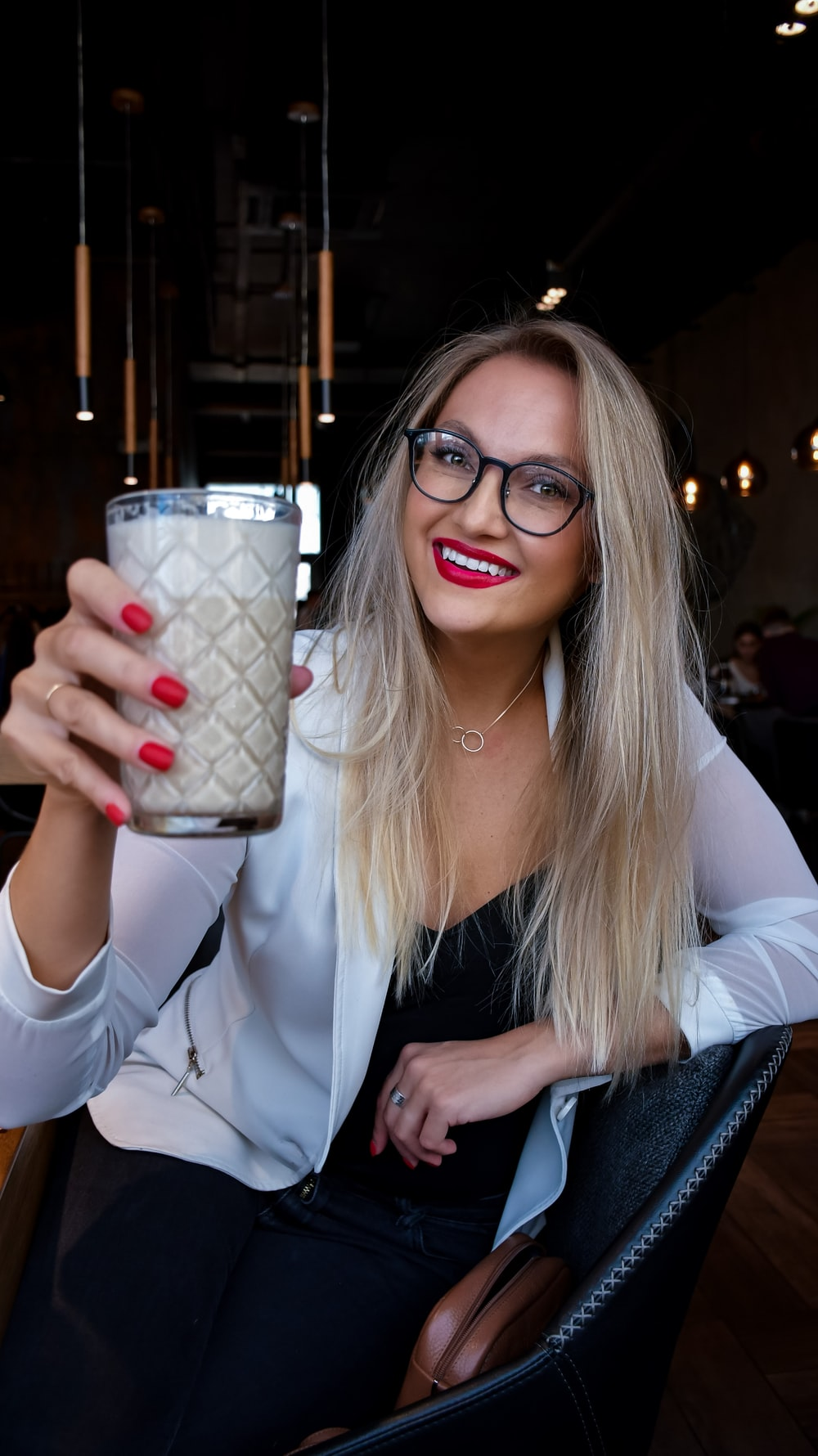 woman in white blazer holding white and red ceramic mug