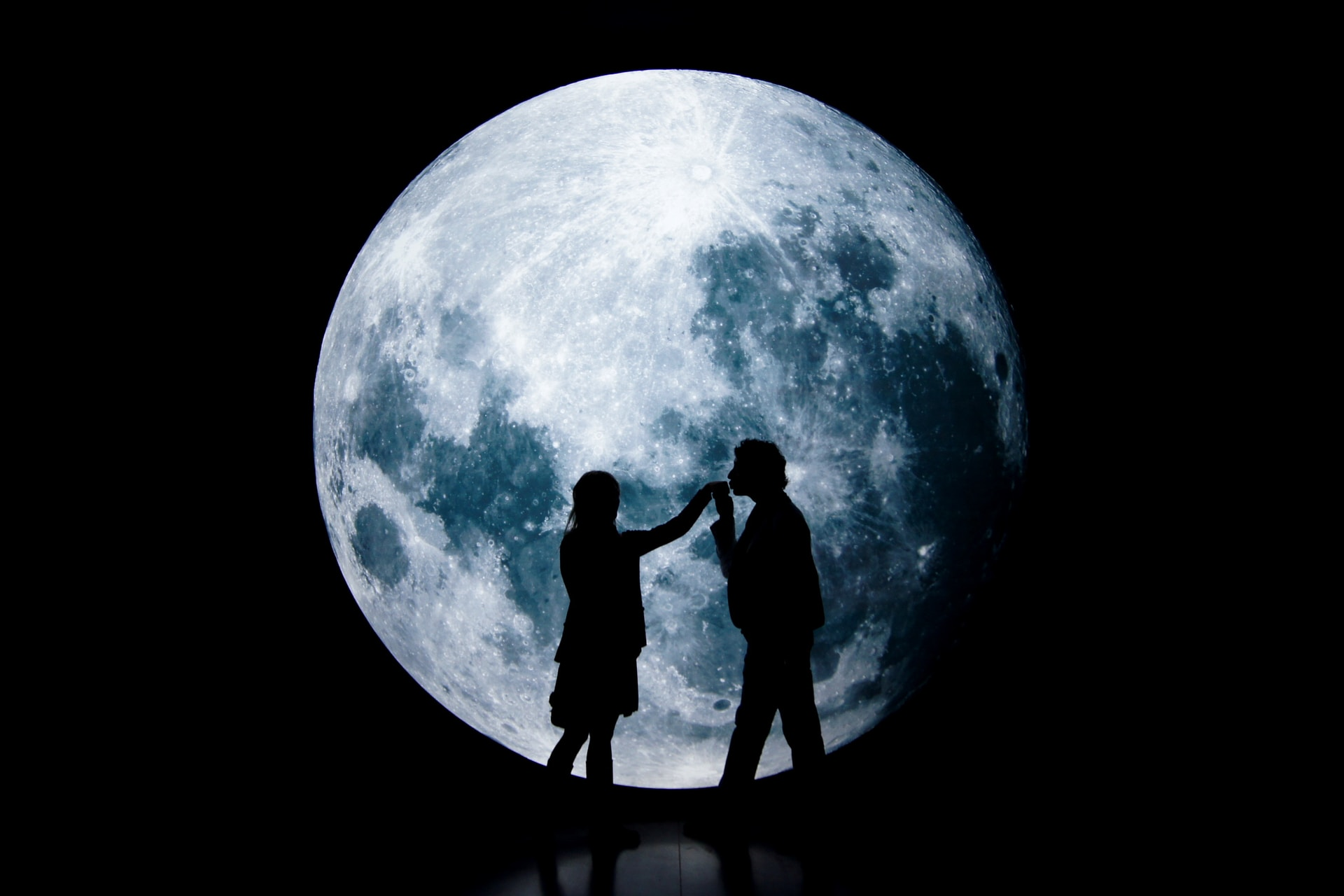 man and woman standing on a round moon