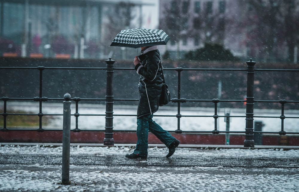 person in black jacket and blue denim jeans holding umbrella walking on snow covered road during
