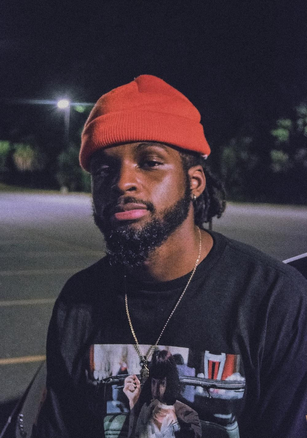 man in black crew neck t-shirt wearing orange cap