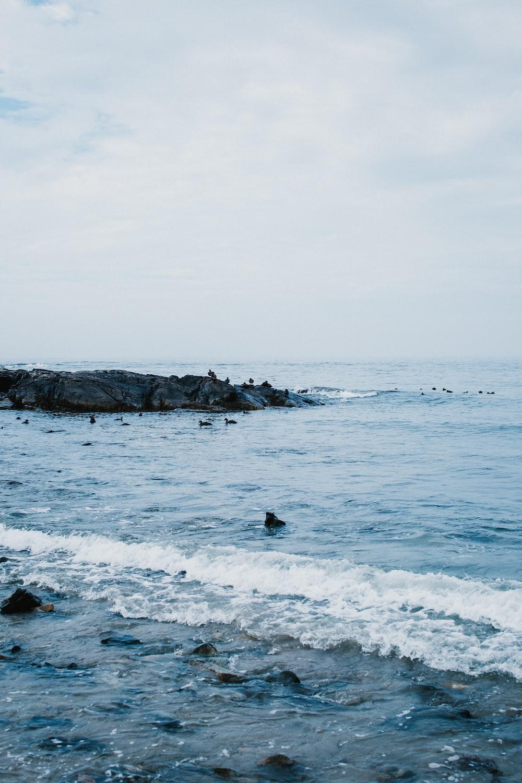 ocean waves crashing on rocks under white cloudy sky during daytime
