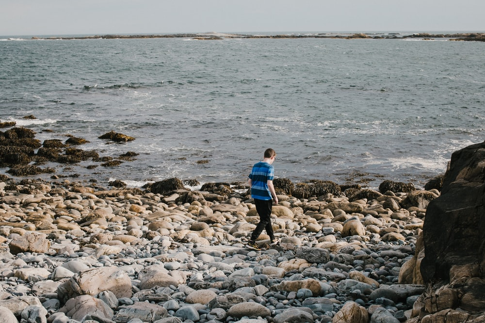 boy in blue shirt and black pants walking on rocky shore during daytime