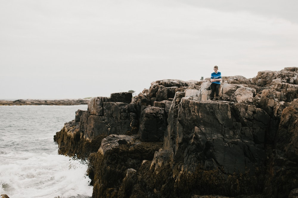 man in blue shirt sitting on rock formation near body of water during daytime