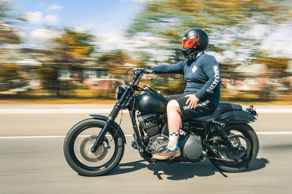 man in blue jacket riding black motorcycle