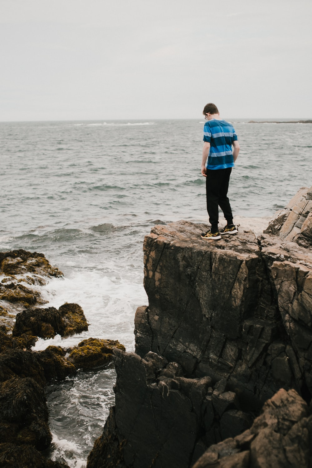 man in blue and black plaid dress shirt standing on rock formation near sea during daytime
