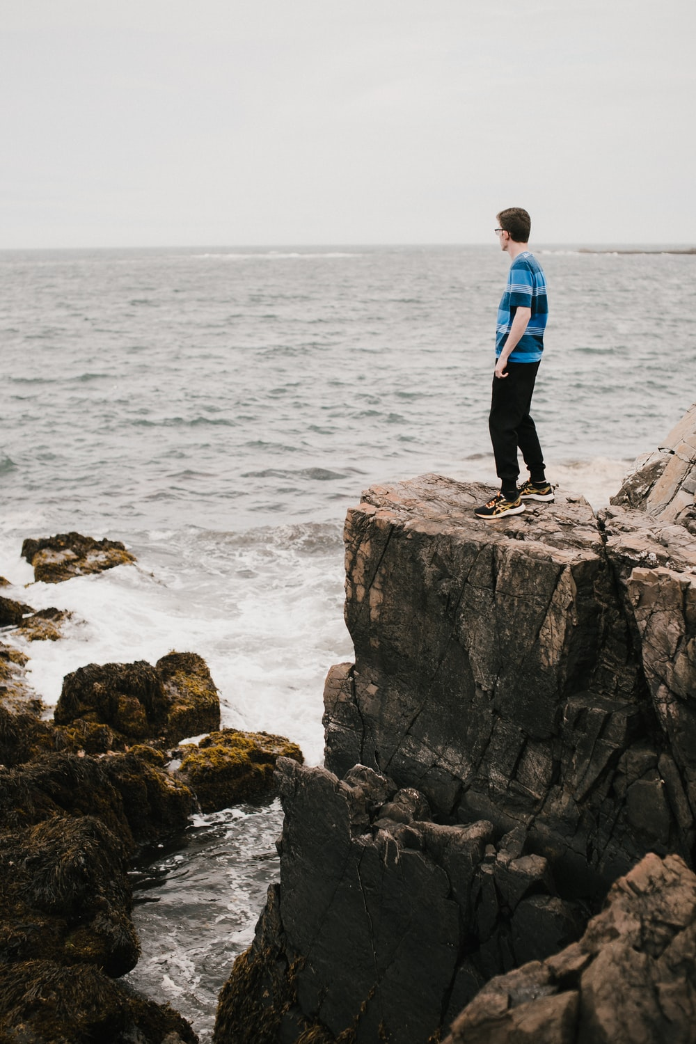 man in blue jacket standing on rock formation near body of water during daytime