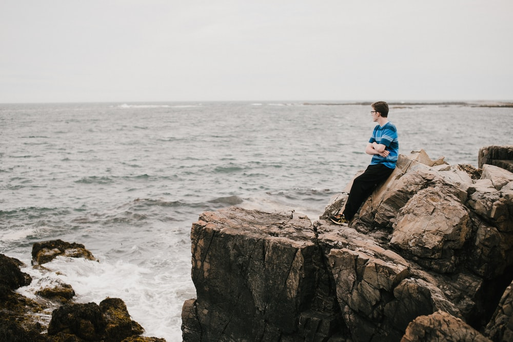 man in blue shirt sitting on rock formation near sea during daytime