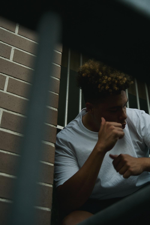 man in white crew neck t-shirt smoking cigarette