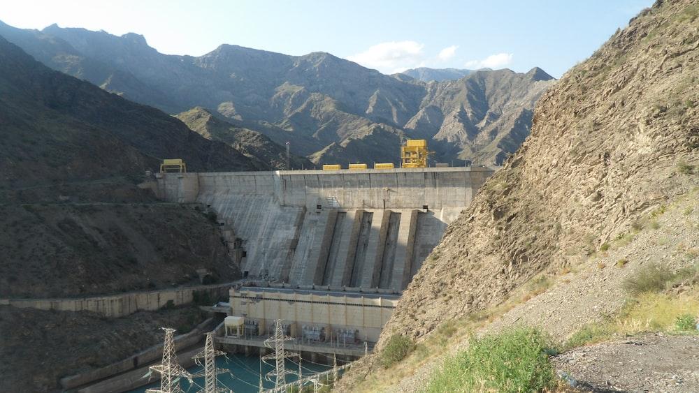 gray concrete dam near mountain during daytime