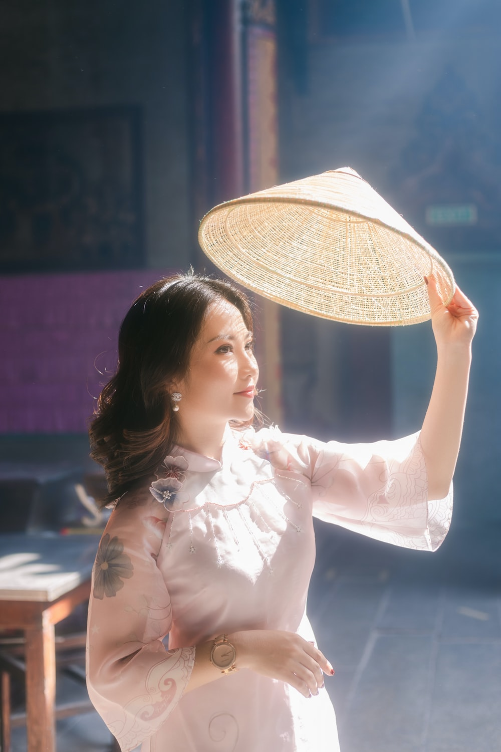woman in white long sleeve shirt holding white hand fan