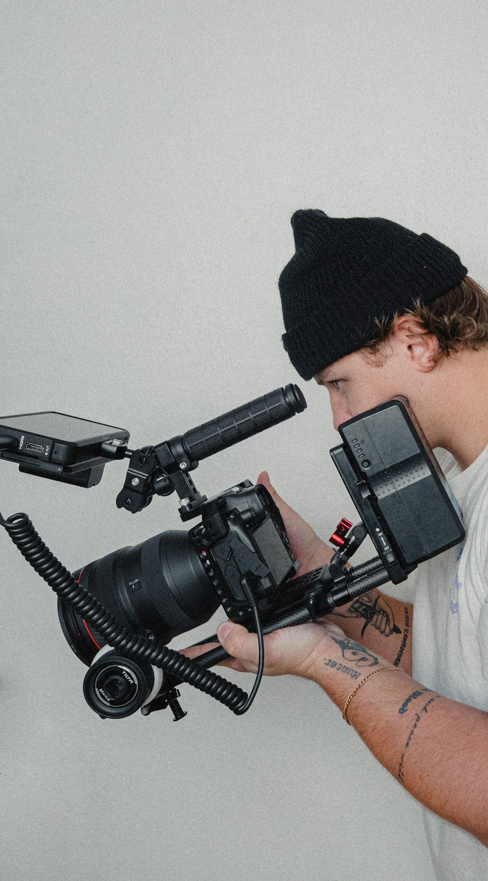 man in black knit cap holding black video camera