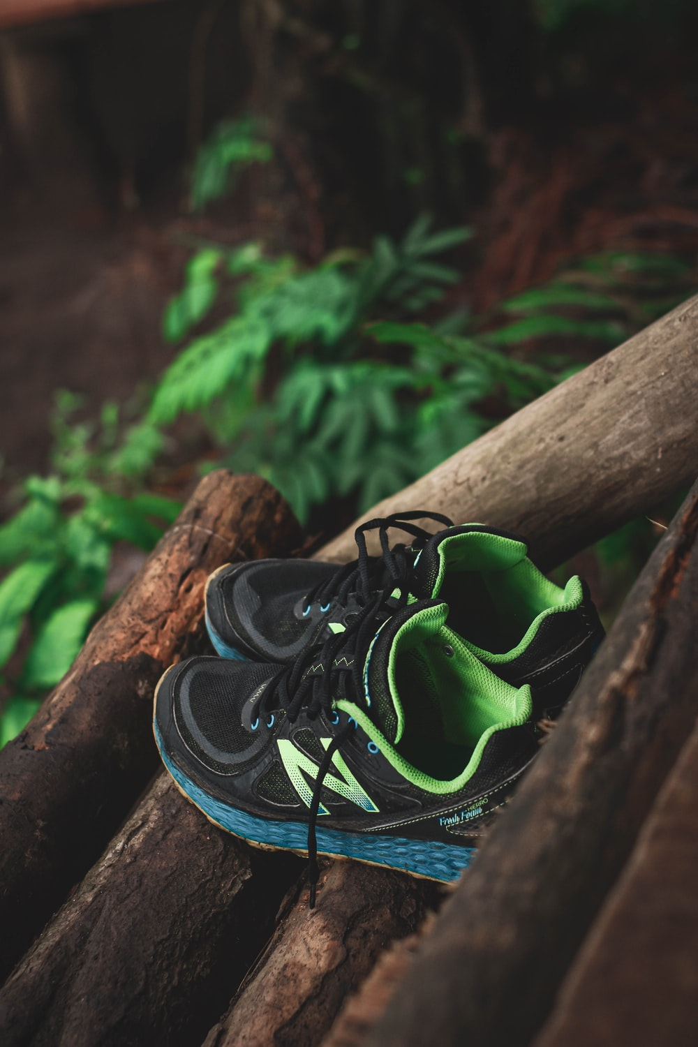 black and green nike athletic shoes on brown wooden log