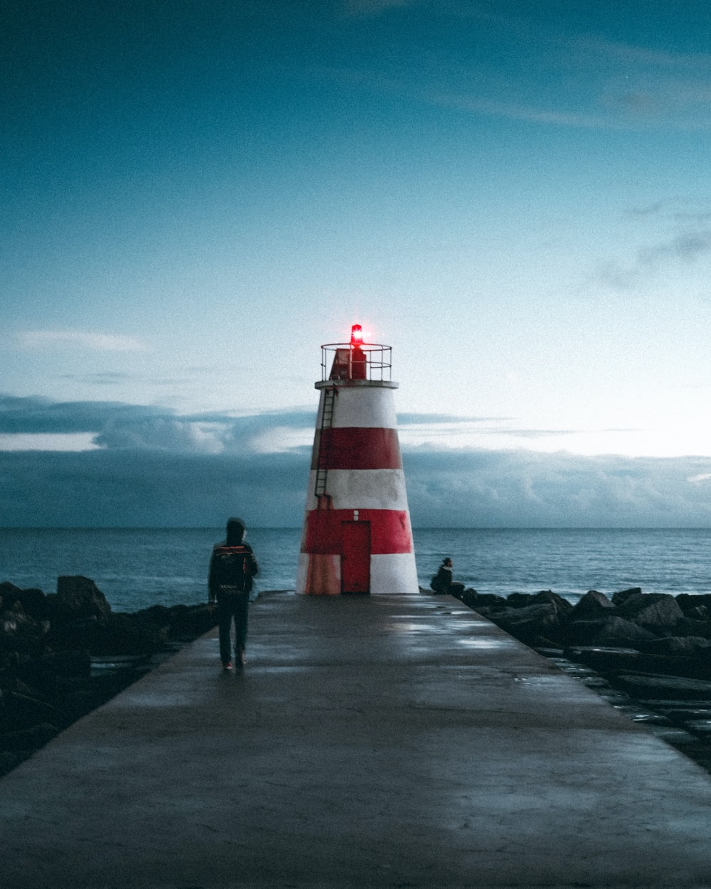 red and white lighthouse near body of water during daytime