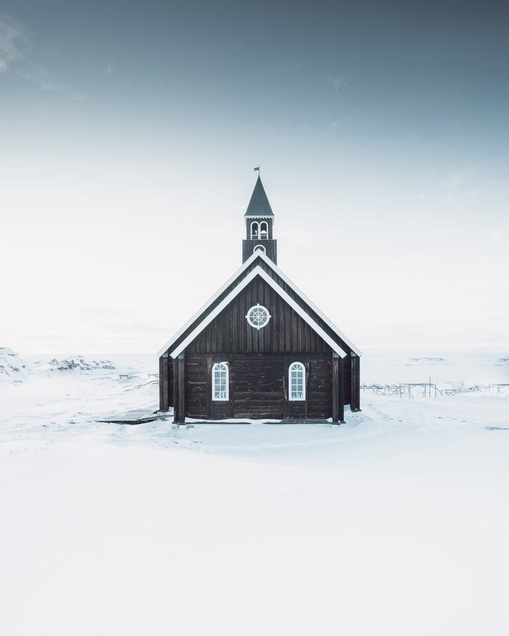 black wooden house on snow covered ground under gray sky