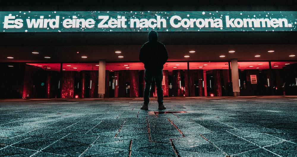 man in black jacket and pants walking on gray concrete floor