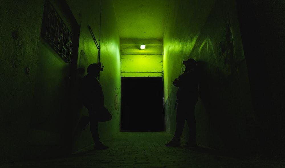 man in black jacket standing near green wall