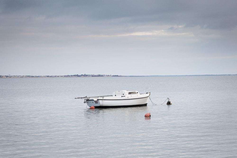 white boat on sea under white sky during daytime