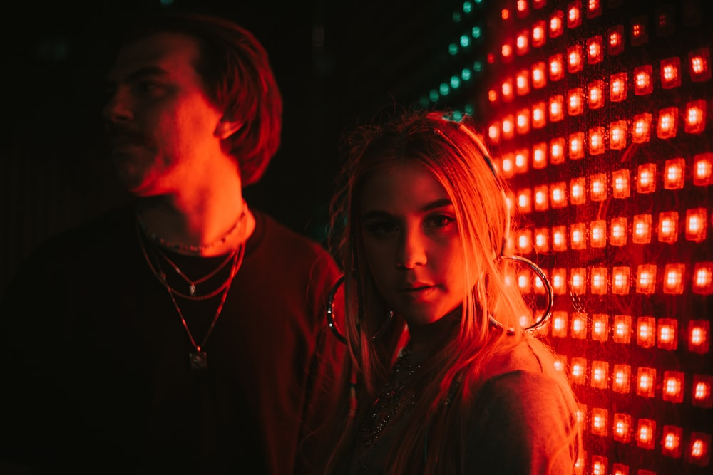 man and woman standing beside red and blue string lights