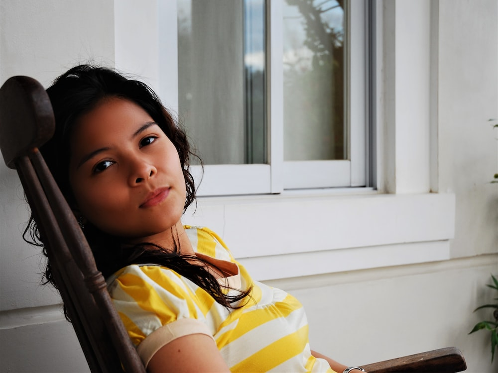 girl in yellow and white stripe shirt sitting on chair
