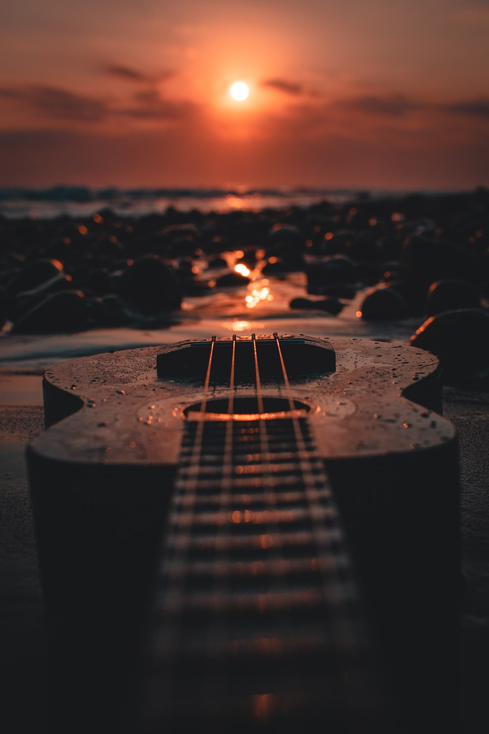 brown acoustic guitar on brown rock during sunset