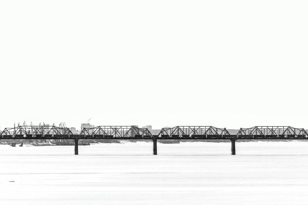 black wooden bridge on white snow field