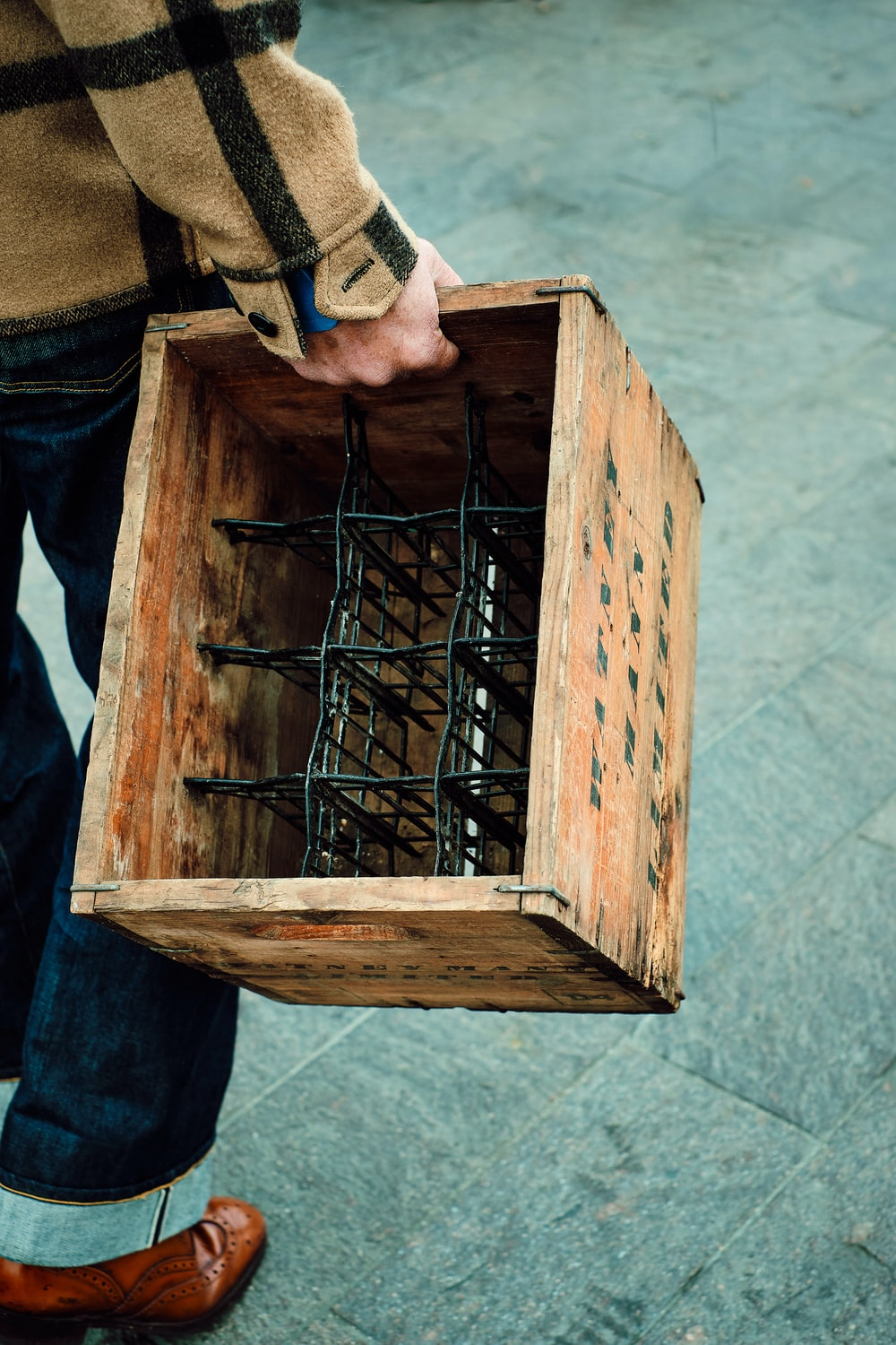 person in blue denim jeans holding brown wooden crate
