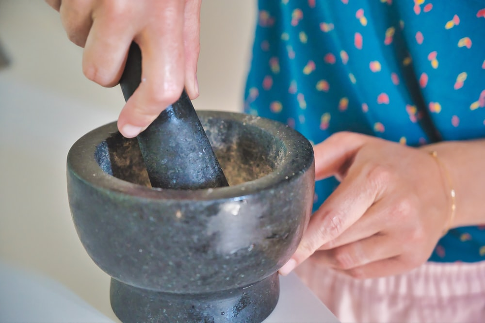 person holding gray mortar and pestle