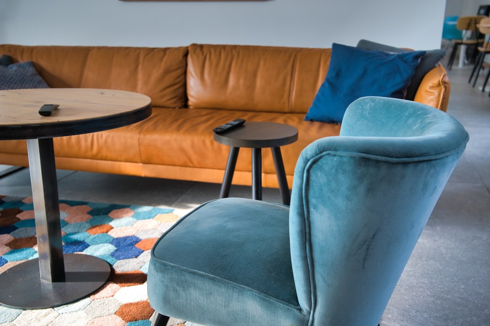 gray padded couch beside brown wooden round table