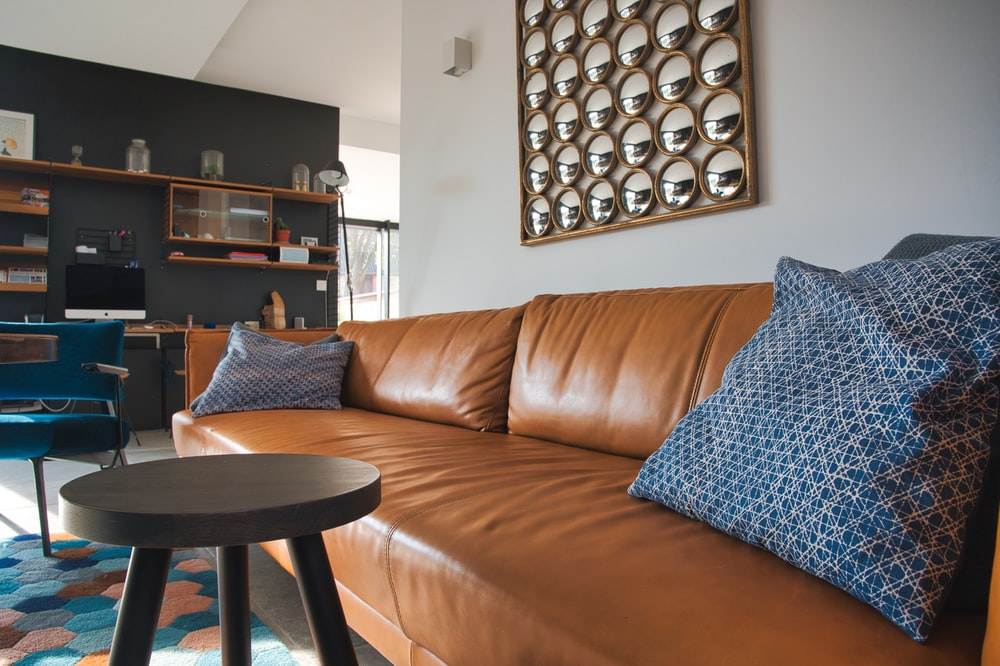 gray throw pillow on brown leather couch