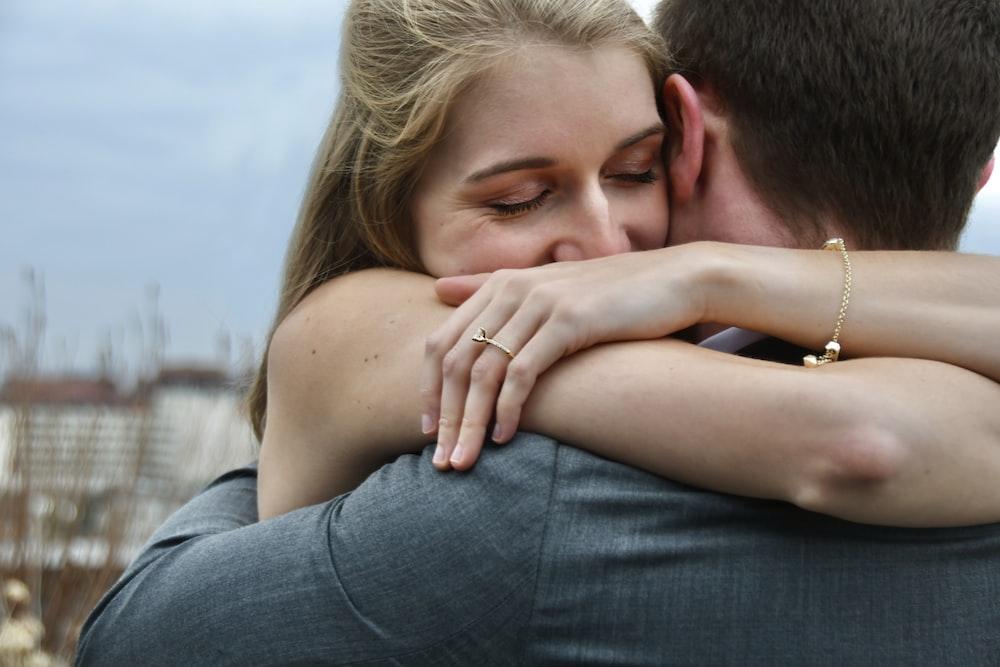 man in blue denim jeans kissing woman in white shirt