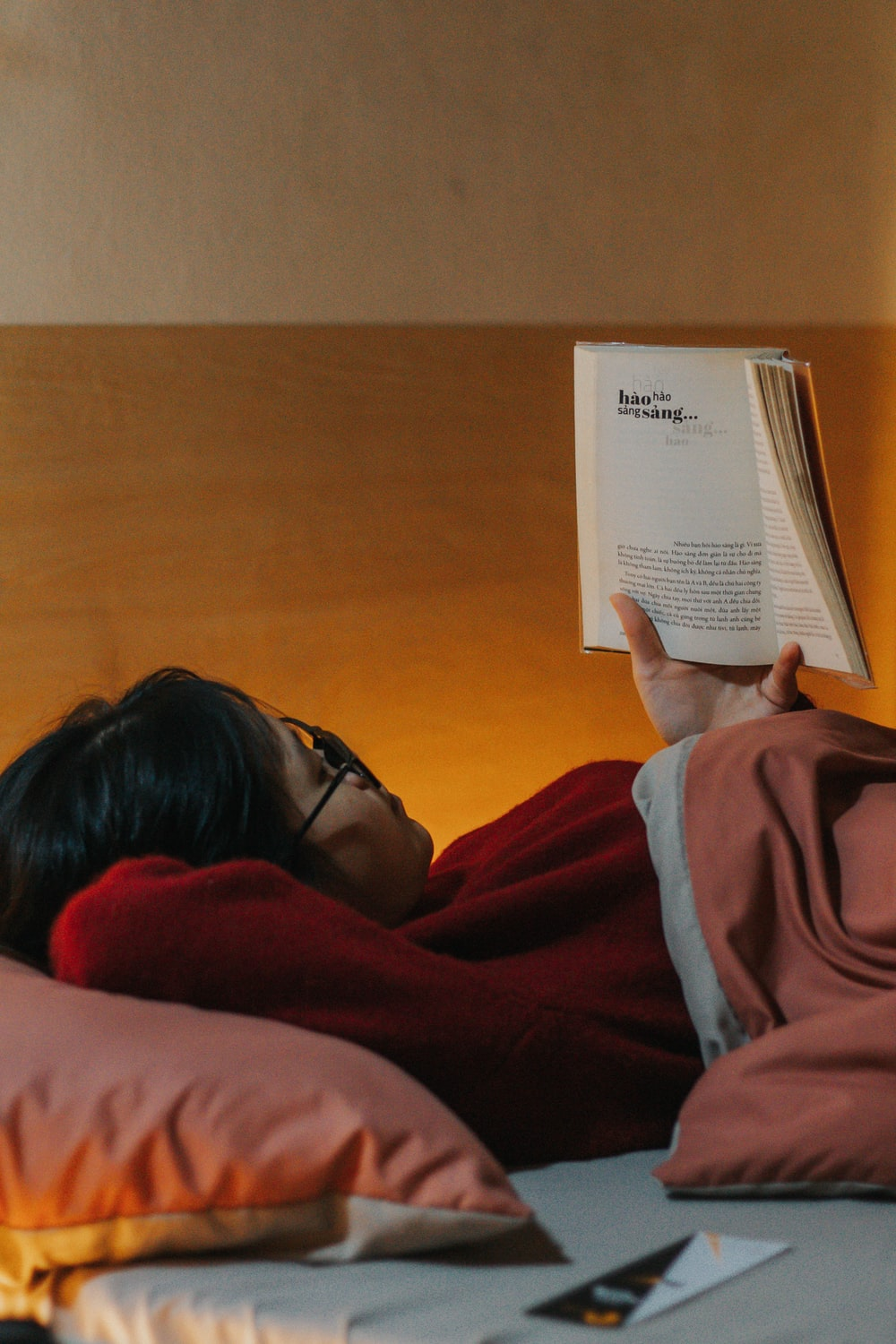 woman in red hoodie reading book