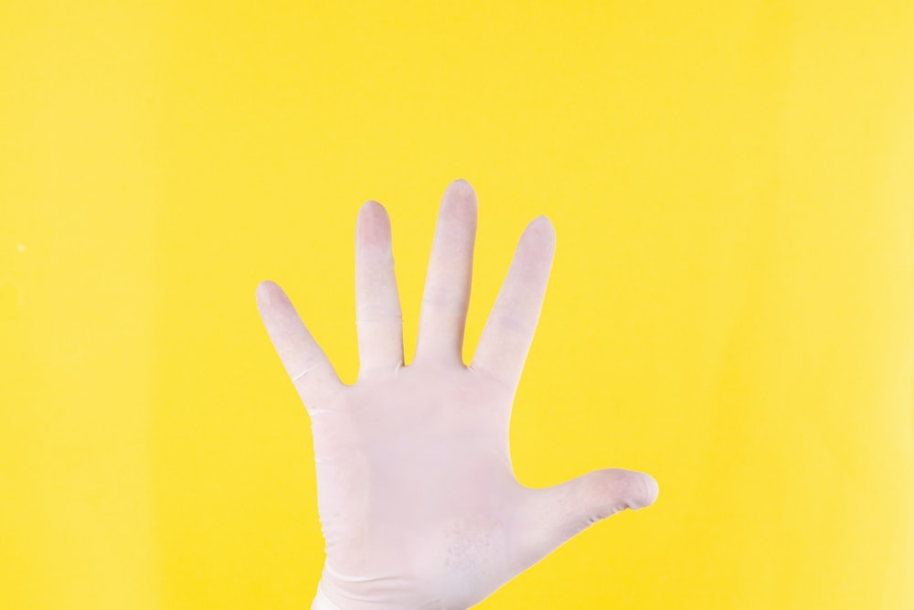 persons left hand on yellow background