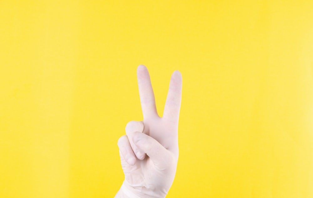 persons hand doing peace sign