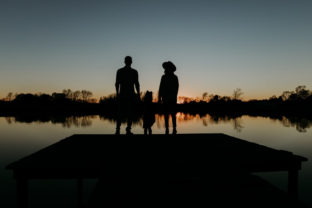 silhouette of 2 person standing on dock during sunset