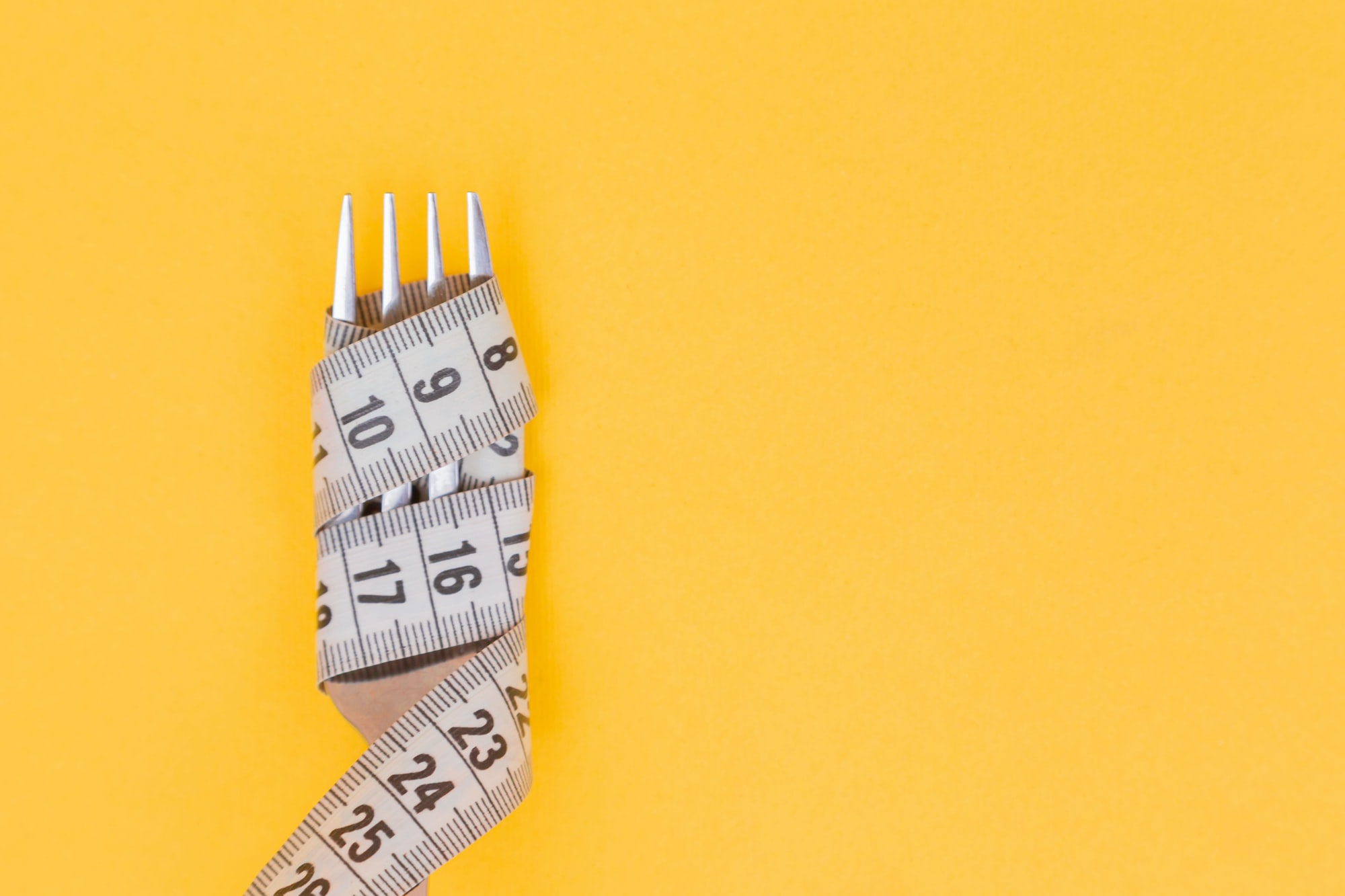 Iron fork and white measuring tape on a yellow background. Diet. Slimming. Obesity. Place for an inscription. Weight loss marathon. Advertising. Top view. The close plan.