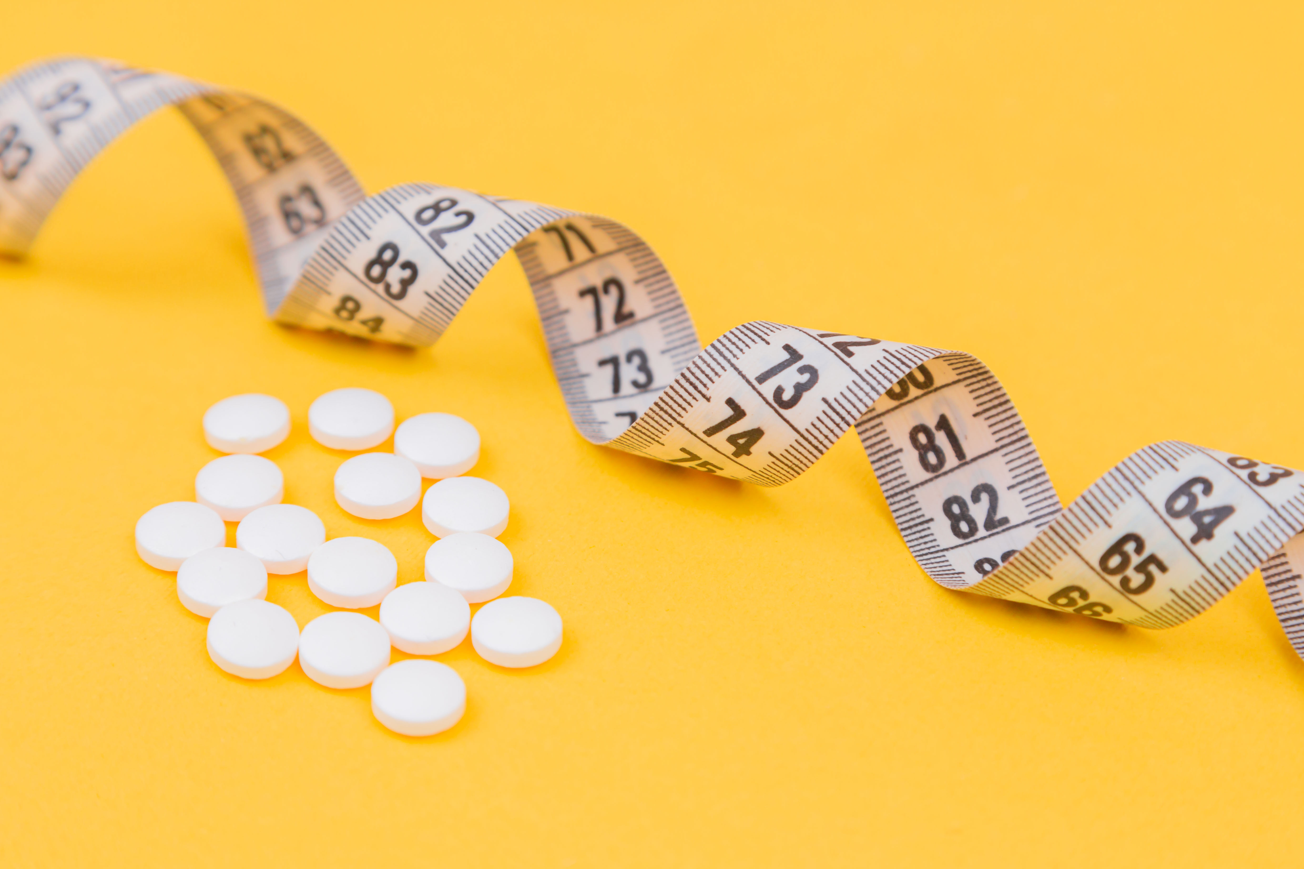White measuring tape with a white pills, white vitamin on a yellow background. Diet. Slimming. Obesity. Place for an inscription. Weight loss marathon. Advertising. Top view. The close plan.